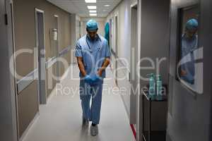 Male surgeon removing rubber gloves while walking at hospital corridor