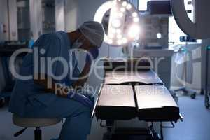 Nervous female surgeon sitting in operation room at hospital