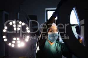 Female surgeon fixing surgical light in operation room at hospital
