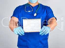 doctor in blue uniform and sterile latex gloves holding open bla
