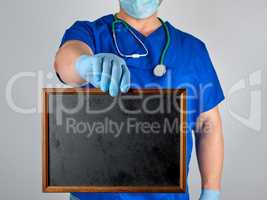 doctor in blue uniform and sterile latex gloves holding a wooden
