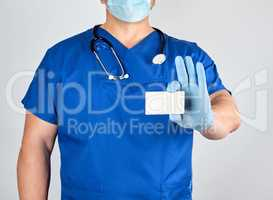doctor in sterile latex gloves and blue uniform holds a blank wh