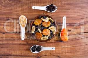 Mix of dried fruits in a wooden bowl over a rustic table