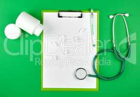 scattered white oval tablets from a plastic jar, stethoscope