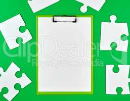 paper clip and white large paper puzzles