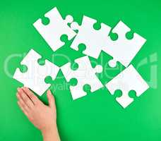 female hand puts empty white big puzzles on a green background