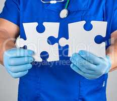 doctor in blue uniform  holds white big blank puzzles
