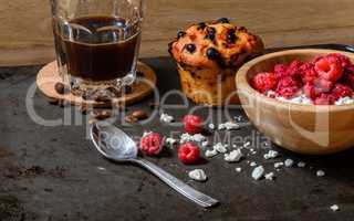 Cottage cheese with raspberries, coffee in a cup and blueberry muffin