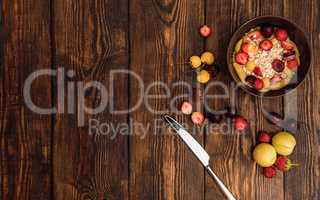 Breakfast with porridge, sweet fruits and berries