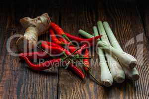 Galangal root, Mexican chili peppers with lemongrass on wooden table