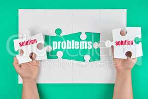 female hand holding white puzzle with the word solution, process