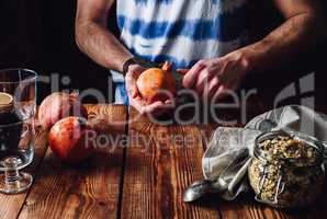 Man Opens Pomegranate with a Knife.