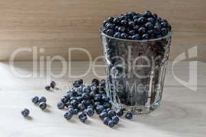 Blueberries in a glass with scattered berries. Good addition for breakfast