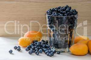 Blueberries in a glass with scattered berries and few apricot