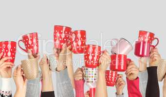 many raised hands up with ceramic cups on a white background