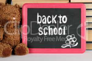 brown teddy bear and black board in red frame