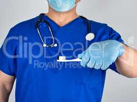 Doctor in sterile latex gloves and blue uniform holding a toothb