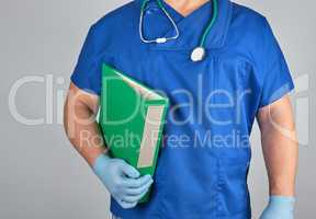 doctor in blue uniform, latex sterile gloves holds in his hand a