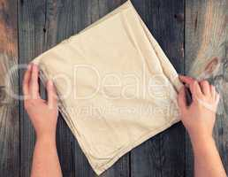 folded beige textile kitchen towel and two hands