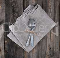 old metal fork and spoon tied with a brown rope on a gray linen
