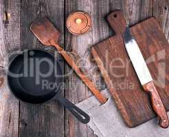empty black round cast iron pan with handle, wooden cutting boar