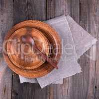 empty round brown carved decorative plate stands on a gray linen
