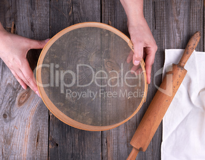 female hands holding a round wooden sieve for flour