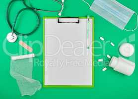paper holder with empty white sheets, medical stethoscope, pills