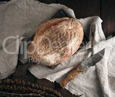 baked oval bread made from rye flour on a wooden cutting board