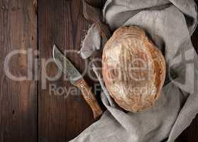 baked oval rye bread on a wooden cutting board