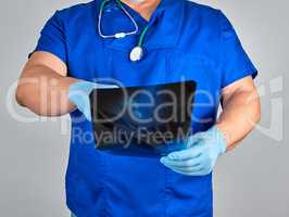 doctor in blue uniform and sterile latex gloves holds and examin