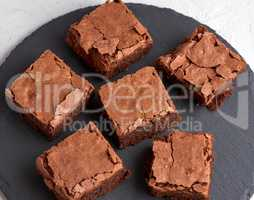 pieces of chocolate brownie on a black round graphite plate