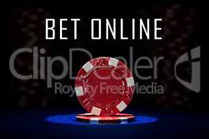 Closeup of red poker chip on blue felt card table surface with spot light on chip