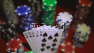 Royal flush on cards and poker chips on red casino table.
