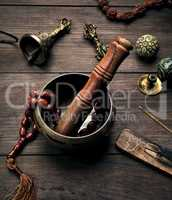 copper singing bowl and a wooden stick on a brown table