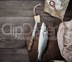 fresh whole sea bass fish on brown cutting board