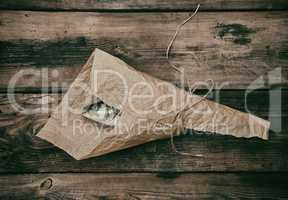 Fresh whole sea bass fish wrapped in a brown paper