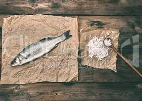 fresh whole sea bass fish on brown crumpled paper