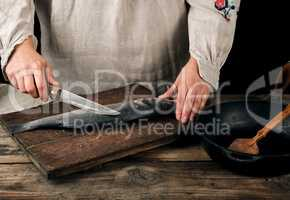 woman in gray linen clothes cleans the fish sea bass scales