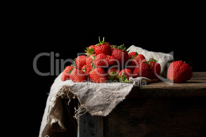bunch of fresh ripe red strawberries on a gray linen napkin