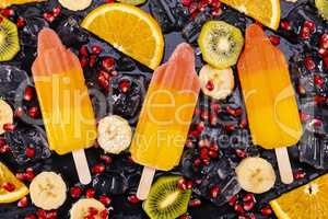 Fruit ice cream on stick with slices fruits on black slate
