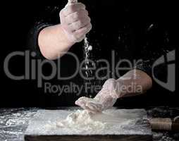 chef in black uniform sifts through his fingers white wheat flou