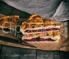 baked pieces of cake with cherries lie on brown paper