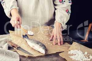 girl in a gray long linen dress holds a full spoonful of salt