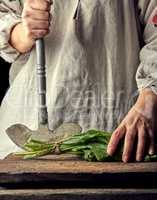 woman in a gray linen dress is cutting green leaves of fresh sor