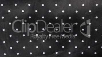 black fabric background with white dots