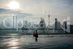 Relaxing in pool and enjoying city panorama. Kuala Lumpur, Malaysia
