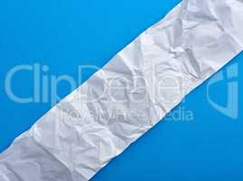 strip of crumpled blank white paper on a blue background