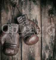 very old leather brown boxing gloves hang on an old shabby woode