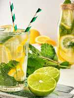 refreshing drink lemonade with lemons, mint leaves, lime in a gl
